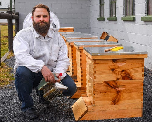 Rich Valley Apiary seller next to beehive